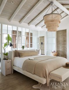 Varying neutral hues fill the bedroom, where a three-tiered coco-bead chandelier from Interior Philosophy hangs from the vaulted ceiling, which features hand-chiseled, rounded beams.