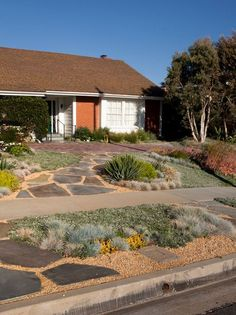 """Of course, xeriscaping doesn't have to be confined to gravel and desert cactus. Beautiful blue flagstone slaps add color, depth, and the backbone of this beautifully diverse front yard."""