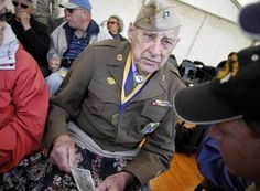A U.S. World War II veteran holds a picture of himself Sunday in Normandy, France, that was taken June 3, 1944.