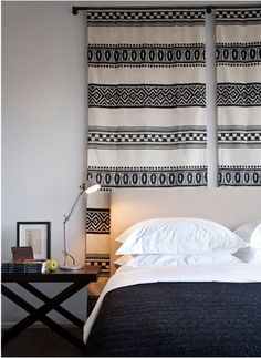 Graphic tapestry/wallhanging adds warmth and texture to a monochromatic bedroom.