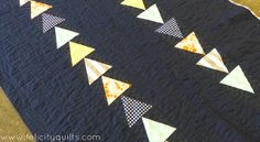 """Up Up and Away is the first finish of 2014 for Felicity from Felicity Quilts and is also her Riley Blake Designs Challenge quilt!   """"For the quilting, I turned to my #Aurifil stash, of course! First, I quilted some wavy lines the length of the quilt using my walking foot and some 28 weight thread in a very, very dark blue (2785). I love the texture it created. Then, around the triangles, I did some loopy loops in a dark grey 50-weight (5004)."""""""