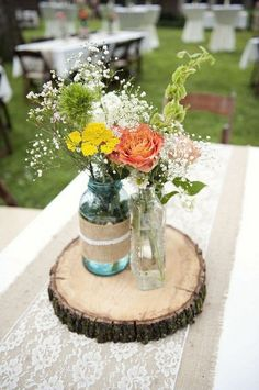 wedding centerpieces with burlap and lace decorated mason jar flower vases on a slice of wood