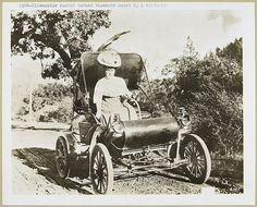 1904 - Oldsmobile, curved dashed runabout model 6, 1 cylinder. Vintage, sapira, photo, woman, female, driver, cool wheels, trees, history, vehicle, transportation.