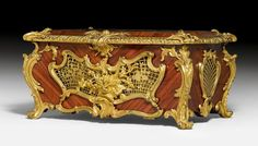 JARDINIERE, Louis XV style, Paris, end of the 19th century. Tulipwood in veneer. Finely pierced walls, the back side hinged. Opulent mounts and applications. Insert, later. Formerly base of a musical clock. 48x33x26 cm. Provenance: - from a private collection, Paris. - Auction Christie's Paris, 14 April 2015 (Lot No. 120). - from a private collection, Berlin. An almost identical jardinière from the 18th century, signed J.F. Oeben and formerly part of the D. Riahi Collection