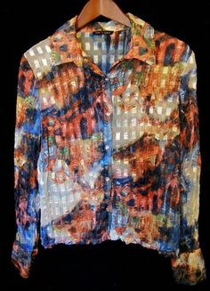 This is a gently worn Violet and Claire designer multi color abstract club long sleeve L Women's Top. This top looks brand new. It buttons up the front. There are six clear buttons on the front. The cuffs have two clear buttons on each. This top is meant to be worn over another top. The abstract colors and design as well as the unusual sheer fabric make this piece a work of art. It is absolutely beautiful.