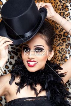 smiling young fashion model posing with a black hat. - Portrait of a smiling young fashion model posing with a black hat, Model: Kiran Bahugun