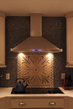 This Cavaliere wall mount range hood looks elegant against the wall and above this range. The range hood also frames the beautiful tile piece decorating this kitchen wall.
