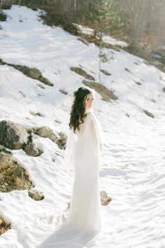 Gorgeous bridal portrait while she is walking into a snowy landscape in Greece