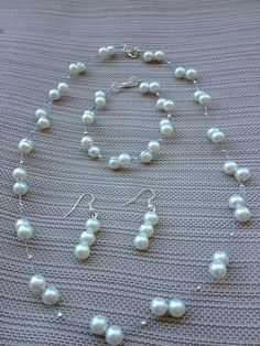 Goin' to the chapel and we're gunna get married'  This exquisite bridal set is made with white glass pearls, intertwined on two strings, and comes with a necklace, bracelet, and a pair of earrings.