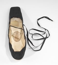 Tiny black slippers were de rigueur in the fashionable mid-Victorian lady's wardrobe. Black shoes were felt to go with anything, hence the most versatile and dependable choice of footwear to have on hand. Slippers of this type are most commonly found in satin, so the faille fabric of this unworn pair is unusual. It is possible that the shoes were intended for mourning, when a dull-surfaced fabric was desired. The interesting label of the London vendor - written largely in French, noting the…