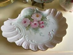 This is a real pretty shaped tray that I painted and signed it from an old mold with all the pretty edges and raised design. Pale pink on border. It is 12x9 in. Each piece I do has been painted and fired many times.
