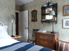 Ben Pentreath's London flat guest bedroom, very English decoration, William Morris Willow Bough paper, Aesthetic Movement shelf