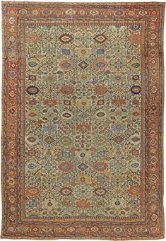 A late 19th century Sultanabad antique rug from West Persia, the cream field with a bold allover pattern of staggered pink, blue, green and beige stylized palmettes separated by floral vinery and rosettes, within a salmon palmette and rosette border.