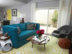 This eclectic gray living room is a mix of color and styles from the teal blue sofa, to the live-edge wood coffee table and midcentury modern chair. The yellow patterned area rug grounds the grouping.