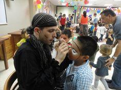 Uno de nuestro animadores maquillando a uno de los niños en una fiesta infantil en carnavales