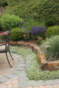 high stone border surrounded by flat pavers with low flowers between (no need to use edger when mowing)