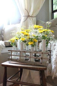 How to make a sunshine filled floral arrangement using supermarket flowers and milk glass vases nestled into a milk bottle holder.