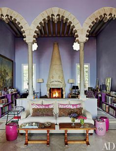 A trio of stone arches creates an enclave at one end of the living room in designer May Daouk's eclectic and colorful Beirut villa. | archdigest.com