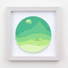 Framed original art. Diorama styled or 2d papercuts layered with paper to make 3d. The shapes are hand cut and then glued together. The image is of a mountain with the hills leading up to it in shades of green. Its like looking at a mountain thats covered in trees and other plants. No actual
