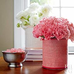 Fill a simple cylinder vase with pretty flowers and wrap the vase with a matching-color piece of burlap. Cut a strip of burlap wide enough to wrap around the cylinder, and line the top and bottom edges and the ends of the burlap with adhesive. Attach the burlap strip to the vase. Cover the top and bottom edges of the burlap with thin velvet ribbon, using fabric glue to secure.