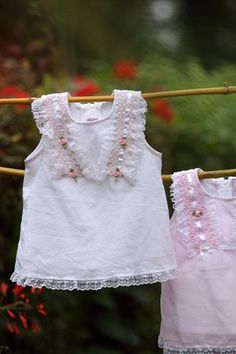 Smocked pieces of fabric form a pretty 'V' pattern on the upper part of the dress that has lovely lace along the border. Tiny satin rose buds and ribbons further make this dress an irresistible attire.