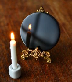 Obsidian scrying mirror with a brass stand, and candle set for divination.