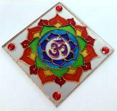 """Mandala em espelho quadrado de 15x15cm, pintura vitral, decorado com pedrinhas em acrílico e tinta relevo dourada. Com gancho para ser pendurado na parede.   Om () É o mantra mais importante do hinduísmo e outras religiões. Diz-se que ele contém o conhecimento dos Vedas e é considerado o corpo sonoro do Absoluto. O Om é o som do universo e a semente que """"fecunda"""" os outros mantras. O mantra Om é a jóia principal entre os outros mantras. Escutar o mantra Om é como escutar o próprio Brahma…"""