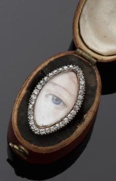 A painted eye portrait ring The glazed marquise-shaped panel painted to depict an eye, within a border of cushion-cut diamonds, the panel later mounted to a late 18th/early 19th century gold shank, with engraved decoration, together with an unassociated Georgian ring box.