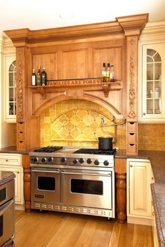 LOVE TUSCAN COLORS, ESP GOLD TILE An ornate, custom wood surround frames the stove area with an arch-shaped opening in this traditional kitchen. Paired with a stunning tile backsplash, the color and detail reminiscent of Italian finery. Small drawers in the surround are perfect for storing easy-to-reach spices and herbs while a small shelf provides easy access to oils and vinegars. The cream cabinetry lets the special design of the surround breath and be eye-catching.