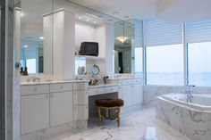 Transitional bathroom mixing modern appointments with traditional painted wood cabinetry. Large dual vanity flanks a central makeup spot, beneath wall to wall mirrors. Large soaking tub at right sits below immense full height windows.
