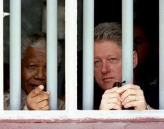 President Clinton and South African President Nelson Mandela peer through the bars of prison cell No. 5, the cramped gray cell where Mandela was jailed for 18 years in his struggle against apartheid.