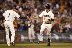 SAN FRANCISCO, CA - SEPTEMBER 09: Buster Posey #28 of the San Francisco Giants is congratulated by third base coach Tim Flannery #1 while rounding the bases after hitting a home run against the Colorado Rockies during the second inning at AT&T Park on September 9, 2013 in San Francisco, California. (Photo by Jason O. Watson/Getty Images)