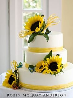 "#1 Not digging the butterflies, but I love the green  leaves coming out from around the sunflowers. It's  a little ""messy"", which reminds me of the look I want for my bouquet. Also, our invitations have that straw-like string (or ribbon?) tied on them. Maybe the top sunflower could be facing the other way, so to act as a backdrop for our topper? I like this!"