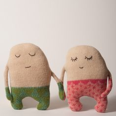 Two little plush people holding hands