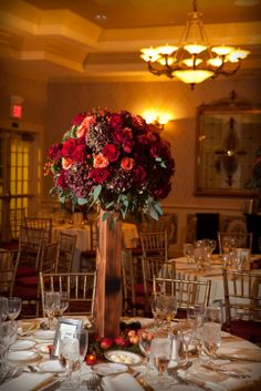 Custom created centerpieces with a rustic wooden base were overflowing at top with antique hydrangea, 'milva', 'black magic' and 'sexy red' roses, along with rose hips and seeded eucalyptus.  Detailed on the table with lady gala apples and moss.