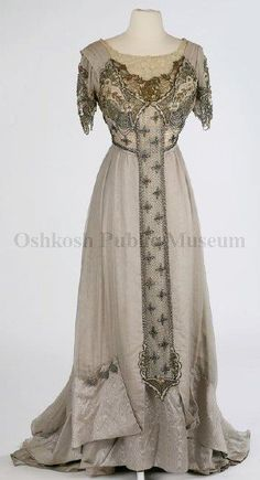 1905 tunic-layered gray gown; bodice neckline of off-white embroidered lace and then gold lace, both front and back bodice decorated with layers of gold, silver and pearl beads and gold sequins also drape just below the bustline, a band of net with strands of beads with beaded flowers flow from a center panel to the bodice back, this center panel extends down the center of the gown both in front and back.