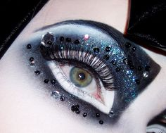 Very bold black and white harlequin like fantasy make-up accented with crystals.