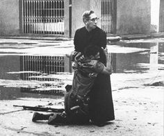 Navy chaplain Luis Padillo gives last rites to a soldier wounded by sniper fire during a revolt in Venezuela. The original title: Aid from the Padre. Taken on 1962.