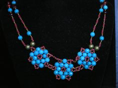 This is a necklace I made, which started out using a pattern for the flowers and then morphed into my own design. SOLD!