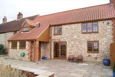 REHAU Golden Oak windows and doors in a stone cottage