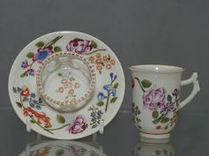 A tiny Du Paquier cup and trembleuse saucer, painted with large sprays of flowers including a full blown puce-pink briar rose, with thorny stems, anemones, orange clovers and an assortment of other small flowers in orange and purple. The reverse of the saucer has three small flower sprays. The central raised gallery is finely pierced copying a metal design, scroll handle and gilded rims  made 1735