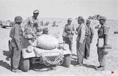 A Afrika Korps officer speaks to soldiers while in his VW Type 82 Kubelwagen