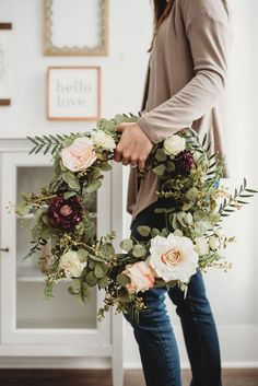 Natural grapevine wreath is adorned with artificial roses, scabiosa, eucalyptus, and rosemary branches.