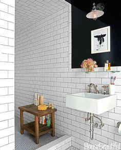 """""""I wanted the nostalgic look of a black-and-white bathroom,"""" Klotz says. """"And I used high-gloss paint"""" — Benjamin Moore's Black — """"because it felt sexy."""" Duravit sink with Rohl fittings. ANNIE SCHLECHTER Parisian Inspired Apartment - Leslie Klotz NYC Apartment - House Beautiful"""