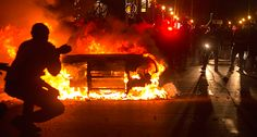 Police are seen near a burning police vehicle after a grand jury returned no indictment in