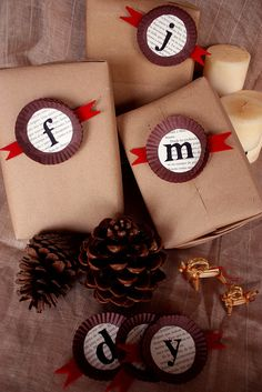 monogrammed gift boxes - looks like cupcake papers cut smaller.       Great idea to put monograms on wrapped Christmas gifts.