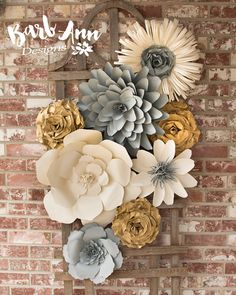 This beautiful collection of handcrafted paper flowers will make a wonderful focal point for any room. With limitless ways to arrange these seven flowers, this piece can fit nearly any space and match most styles of home décor. Its also an ideal decoration for a wedding venue, bridal or baby shower, christening party, or any other celebration.  The flowers are individually crafted from heavy weight cardstock. Each one is secured by a versatile ribbon hanger for use with push pins or hooks to…