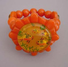 "BAKELITE apple juice reverse carved and painted fishes center with round with orange beads stretchy bracelet, 6-7/8"" when relaxed by 2"" at the front and 1"" at the back, circa 1940."