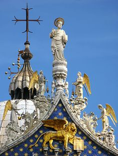 Detail of the rooftop of San Marco cathedral in Venice, Italy. Venice patron Saint, St. Mark with angels. Underneath is winged lion, mascot of Venice.