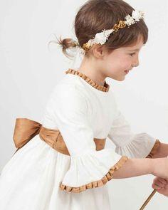 Vestido de ceremonia para niña modelo Rita en otomán y manga campana. Fajín de tablas con lazos y ribetes de cuello y mangas en shantung cobre.
